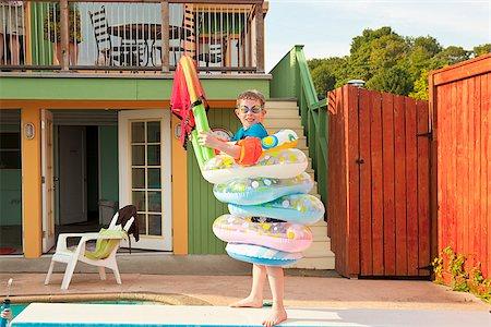 Boy wearing multiple life rings poolside Stock Photo - Premium Royalty-Free, Code: 673-03005417
