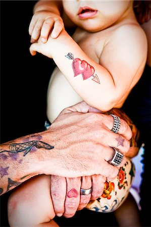 tattoed arms holding tattoed baby Stock Photo - Premium Royalty-Free, Code: 673-03405714