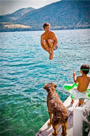 man doing cannonball into lake Stock Photo - Premium Royalty-Free, Code: 673-03405733