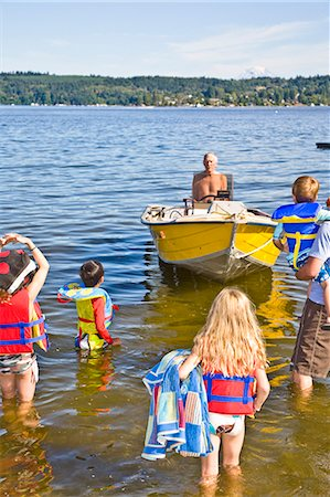 family wading out to motorboat Stock Photo - Premium Royalty-Free, Code: 673-03405796