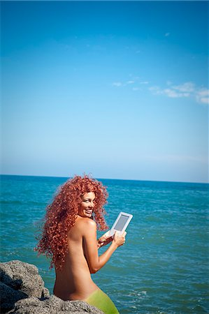 woman by sea with e-book Stock Photo - Premium Royalty-Free, Code: 673-03623045