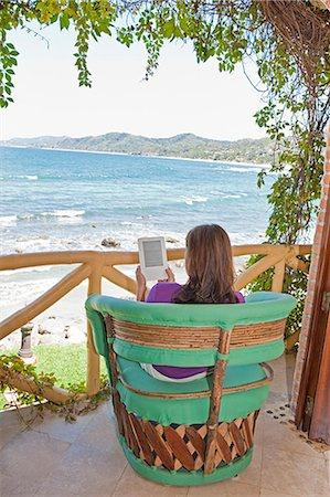 woman reading e-book on balcony Stock Photo - Premium Royalty-Free, Code: 673-03623155