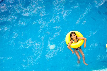 girl in yellow life ring in pool Stock Photo - Premium Royalty-Free, Code: 673-03826281