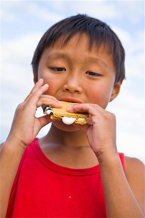 boy eating s'more outdoors Stock Photo - Premium Royalty-Free, Code: 673-03826297