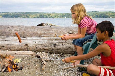 children roasting hotdogs over beach fire Stock Photo - Premium Royalty-Free, Code: 673-03826299