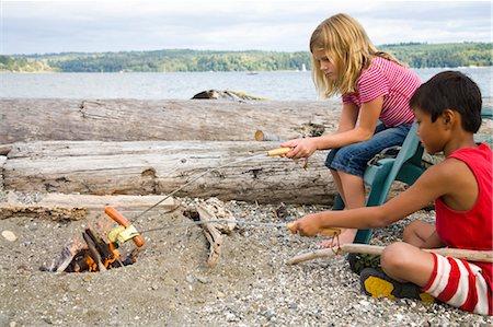 children roasting hotdogs over beach fire Stock Photo - Premium Royalty-Free, Code: 673-03826300