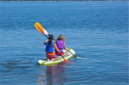 girls on paddle board in lake Stock Photo - Premium Royalty-Free, Code: 673-03826325