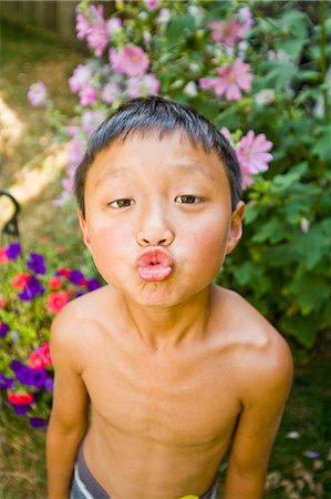 preteen kissing - asian boy with puckered lips outdoors Stock Photo - Premium Royalty-Free, Code: 673-03826322