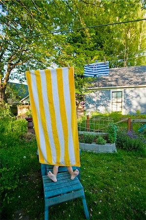 boy on garden chair under beach towel Stock Photo - Premium Royalty-Free, Code: 673-03826362