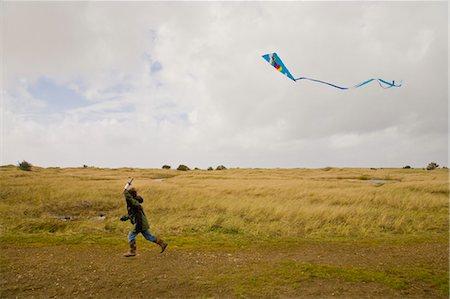 boy running with kite in air Stock Photo - Premium Royalty-Free, Code: 673-03826377