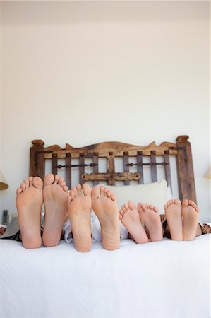 family lying on bed, feet lined up Stock Photo - Premium Royalty-Free, Code: 673-03826417