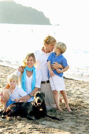 dog kissing man - portrait of family on beach with dogs Stock Photo - Premium Royalty-Free, Code: 673-03826436