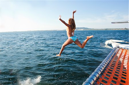 woman jumping off yacht into sea Stock Photo - Premium Royalty-Free, Code: 673-03826474