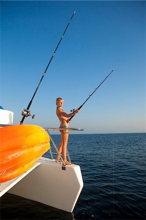 young woman with fishing pole on yacht Stock Photo - Premium Royalty-Free, Code: 673-03826484