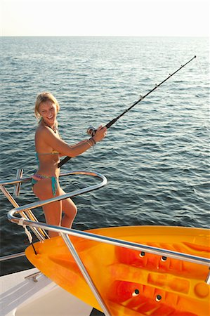 young woman with fishing pole on yacht Stock Photo - Premium Royalty-Free, Code: 673-03826485