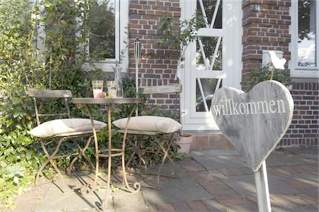 Sign and table with chairs at house entrance Stock Photo - Premium Royalty-Free, Code: 689-05610970