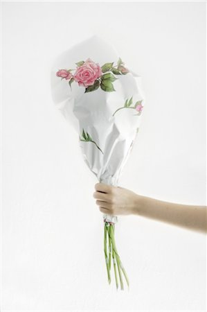 present wrapped close up - Hand holding wrapped bunch of flowers Stock Photo - Premium Royalty-Free, Code: 689-05611532