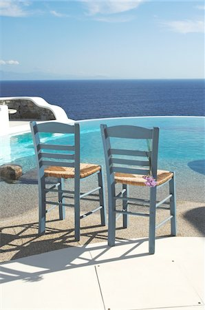 Two chairs by the poolside above the ocean Stock Photo - Premium Royalty-Free, Code: 689-05611734