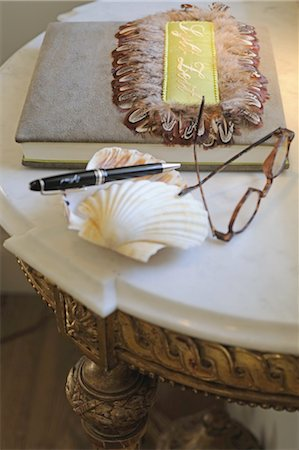 Eyeglasses, decorative seashell, pen and book on table Stock Photo - Premium Royalty-Free, Code: 689-05611853