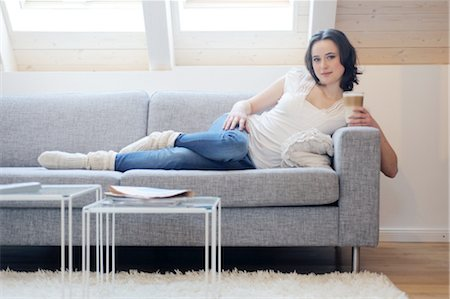 Young woman on couch drinking Latte Macchiato Stock Photo - Premium Royalty-Free, Code: 689-05611949