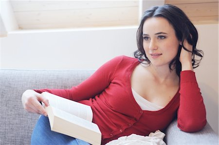 dreamy - Young woman reading book on couch Stock Photo - Premium Royalty-Free, Code: 689-05611958
