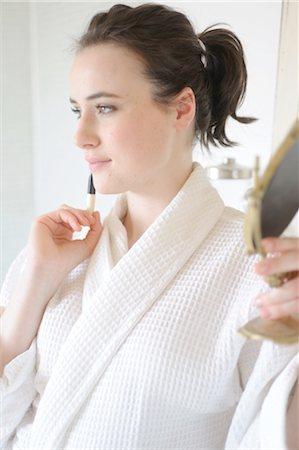 personal care - Young woman applying blush in bathroom Stock Photo - Premium Royalty-Free, Code: 689-05611982