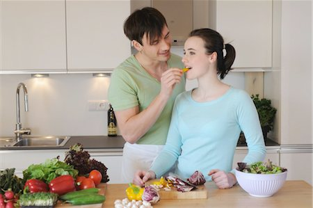 Young couple in kitchen preparing salad Stock Photo - Premium Royalty-Free, Code: 689-05611998
