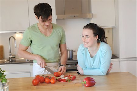Young couple in kitchen slicing vegetables Stock Photo - Premium Royalty-Free, Code: 689-05612004