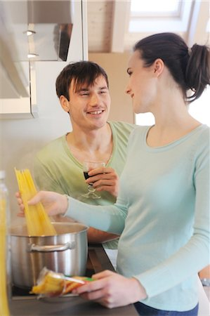 Young couple in kitchen cooking spaghetti and drinking red wine Stock Photo - Premium Royalty-Free, Code: 689-05612011