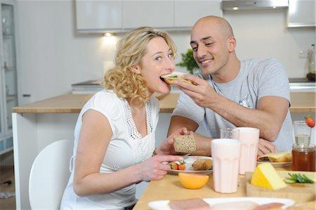 Happy couple having breakfast in kitchen Stock Photo - Premium Royalty-Free, Code: 689-05612036