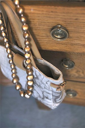 Handbag and necklace hanging at dresser Stock Photo - Premium Royalty-Free, Code: 689-05612446