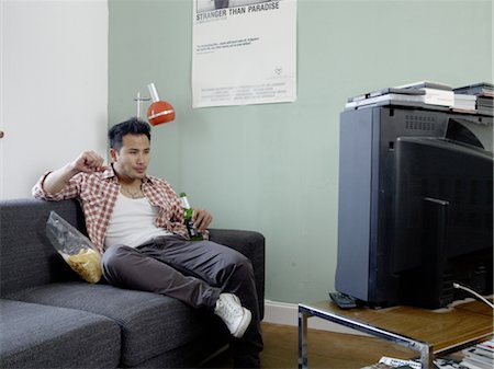 Man watching TV with beer and chips Stock Photo - Premium Royalty-Free, Code: 689-05612543