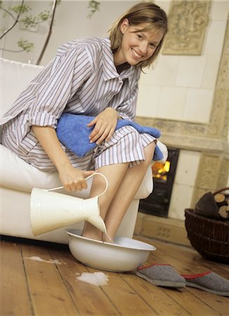 Woman in pajamas taking footbath Stock Photo - Premium Royalty-Free, Code: 689-05612594