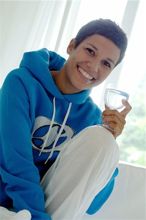 drinking water glass - Young woman holding glass of water on couch Stock Photo - Premium Royalty-Free, Code: 689-05612735