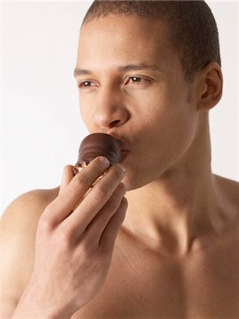 Barechested man eating chocolate marshmallow Stock Photo - Premium Royalty-Free, Code: 689-03733094