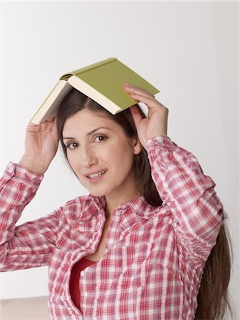 Woman holding book above her head Stock Photo - Premium Royalty-Free, Code: 689-03733182