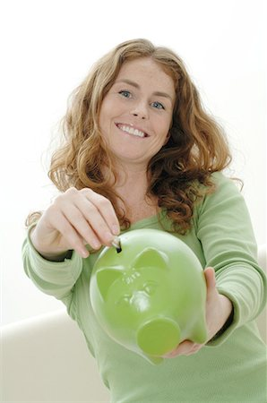 Woman putting coin into piggy bank Stock Photo - Premium Royalty-Free, Code: 689-03733390