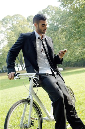 Businessman with bicycle and cell phone in park Stock Photo - Premium Royalty-Free, Code: 689-03733401