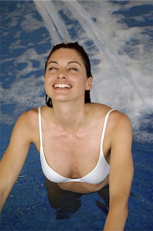 Woman in swimming pool under jet of water Stock Photo - Premium Royalty-Free, Code: 689-03733615