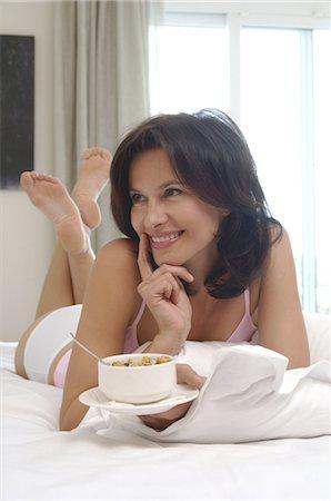 Woman eating muesli in bed Stock Photo - Premium Royalty-Free, Code: 689-03733616