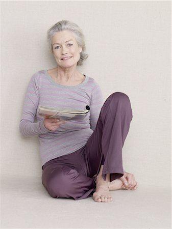 Senior woman with magazine sitting on floor Stock Photo - Premium Royalty-Free, Code: 689-03733666