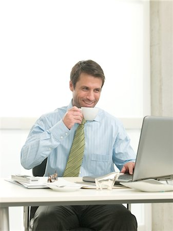 Businessman at desk drinking coffee Stock Photo - Premium Royalty-Free, Code: 689-03733759