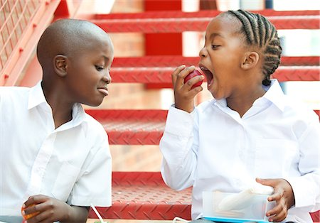 preteen open mouth - Boy and girl eating apple on steps outside school, Johannesburg, Gauteng Province, South Africa Stock Photo - Premium Royalty-Free, Code: 682-05649946