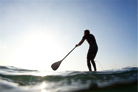 side view of person rowing in boat - Stand-up paddle boarder paddling on sea, Durban, KwaZulu-Natal Province, South Africa Stock Photo - Premium Royalty-Free, Code: 682-05649984