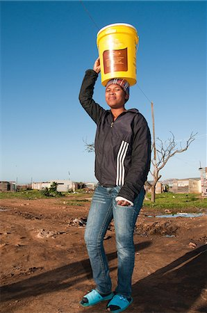 Young woman carrying water to house, Missionvale, Port Elizabeth, Eastern Cape Province, South Africa Stock Photo - Premium Royalty-Free, Code: 682-05650384