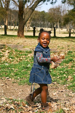pile leaves playing - Toddler girl walking with handful of autumn leaves in her hands and smiling broadly, Johannesburg, South Africa Stock Photo - Premium Royalty-Free, Code: 682-05650595