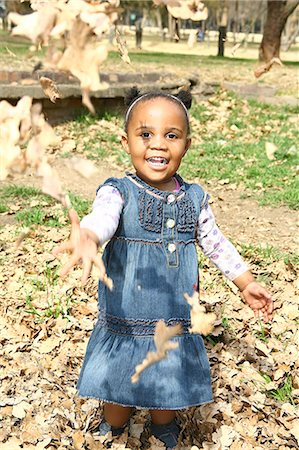 pile leaves playing - Toddler girl throwing autumn leaves up in air and smiling broadly, Johannesburg, South Africa Stock Photo - Premium Royalty-Free, Code: 682-05650593