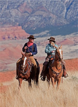 Cowboy and cowgirl riding through Hideout Ranch in Shell, Wyoming, USA Stock Photo - Premium Royalty-Free, Code: 682-05976924