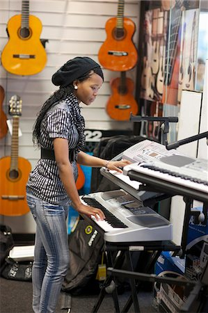 A young woman playing a keyboard in a music shop, Pietermaritzburg, KwaZulu-Natal, South Africa Stock Photo - Premium Royalty-Free, Code: 682-05977187