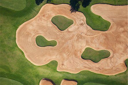An aerial of a large, well manicured bunker on a golf course. Stock Photo - Premium Royalty-Free, Code: 682-06374444